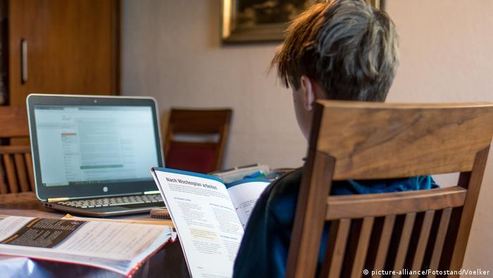 Ein Junge sitzt mit einem Buch und einem Laptop am Tisch