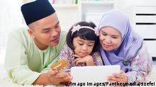 Southeast Asian family using tablet pc computer online shopping with credit card at home. Muslim family living lifestyle. Happy smiling Malay parents and child. model released Symbolfoto PUBLICATIONxINxGERxSUIxAUTxONLY Copyright: xszefeix Panthermedia09477408