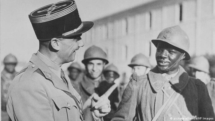 A historical photo showing a French officer speaking with a Senegalese soldier