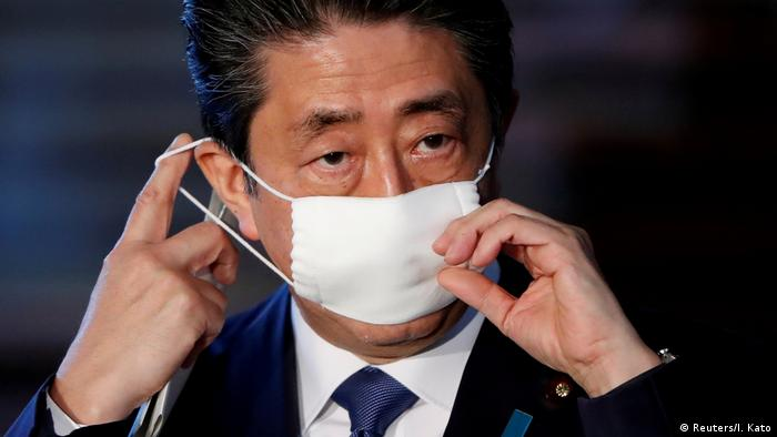 Japan's Prime Minister Shinzo Abe adjusts his face mask