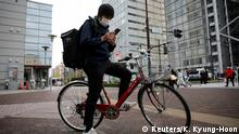 Taiga Fukutani, a comedian whose entertainment bookings dried up following the coronavirus disease (COVID-19) outbreak, works as an Uber Eats delivery man in Tokyo, Japan April 16, 2020. REUTERS/Kim Kyung-Hoon