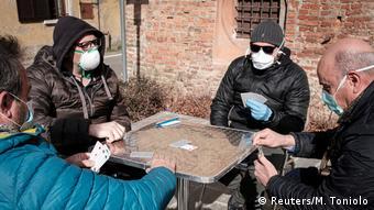 Четверо мужчин в масках играют в карты в итальянском Сан-Фьорано