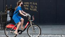 A woman cycles past graffiti stating that 'Covid 19 is a hoax and 5G is the killer'. Piccadilly Circus, London, England, UK on Wednesday 15 April, 2020. Conspiracy theorists have been suggesting that the rollout of 5G is the real reason people are dying and that Coronavirus is not real. A lockdown has been imposed by British Prime Minister Boris Johnson top stop the spread of Coronavirus (Covid-19) which has seen few people venture out into the streets. Picture by Justin Ng/UPPA/Avalon |
