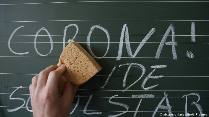 A hand erases the words 'Corona' on a chalkboard