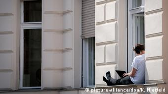 A man sits on his window sill and works on his laptop