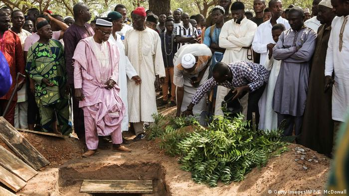 Mourners in Ghana stand around an open grave