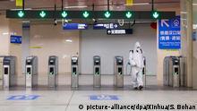 23.03.2020, China, Wuhan: Ein Mitarbeiter in Schutzanzug desinfiziert in Wuhan in der Provinz Hubei eine U-Bahn-Station. Personen, welche die öffentlichen Verkehrsmittel oder Taxis in Wuhan nutzen möchten, müssen sich zuvor mit ihrem Klarnamen registrieren lassen, so die Behörden am Sonntag (22.03.2020). Zum ersten Mal seit dem Ausbruch des neuartigen Coronavirus hatte China vergangene Woche erstmal landesweit keine lokalen Neuinfektionen mehr gemeldet. Foto: Shen Bohan/XinHua/dpa +++ dpa-Bildfunk +++