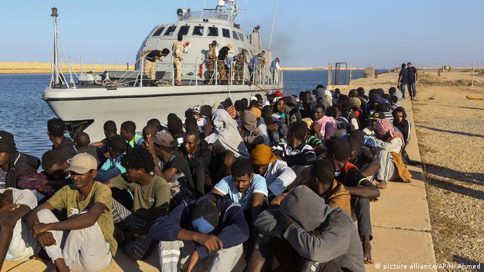 Libyen Khoms Migranten neben Boot der Küstenwache