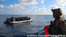 In this image provided by the Turkish Military, a member of Turkish forces, right, on a boat approaches migrants aboard a dinghy in the mid Mediterranean Sea, Wednesday, Jan. 29, 2020. The military said that a military ship, TCG Gaziantep, assisted the migrants and provided medical aid before handing them over to the Libyan Coast Guard. The frigate is in the region to support NATO's Mediterranean Shield Operation and to assist NATO's Marine Guard Operation. (Turkish Military via AP)