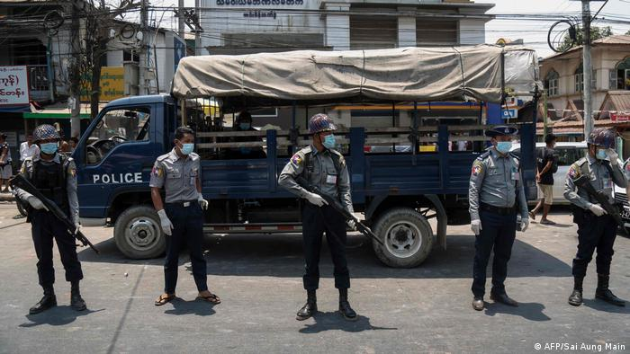 Police, wearing face masks as a preventive measure against the spread of the COVID-19 novel coronavirus, stand guard during a prisoner release in front of Insein Prison in Yangon on April 17, 2020