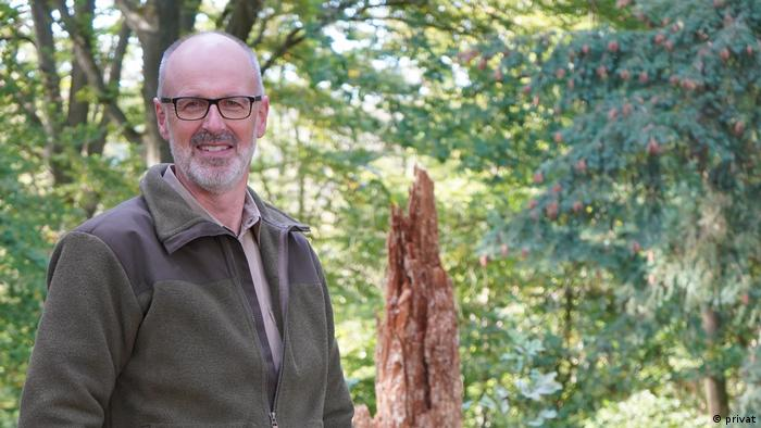 Peter Wollleben wears glasses and stands in a forest