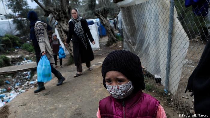 Lesbos, Grecia: un niño con mascarilla entre ruinas de un campamento para refugiados.