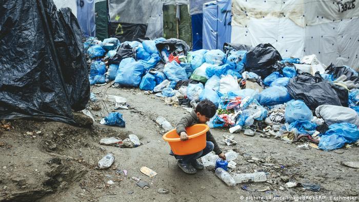 Fotoğrafta Moria mülteci kampında çöplerin içindeki bir çocuk görünüyor.