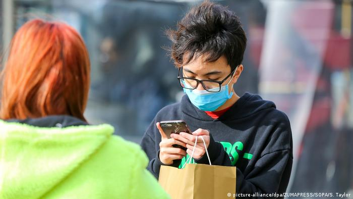 A man wearing a face mask as a preventive measure against the coronavirus views his mobile phone in central London