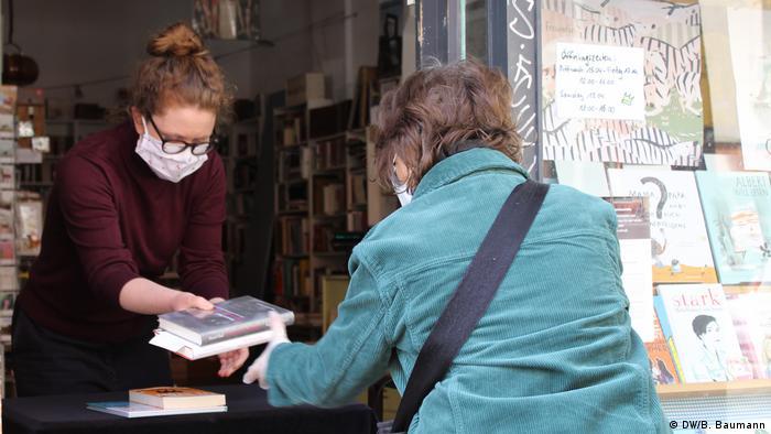 Nina Wehner von der Buchhandlung Die Buchkönigin in Berlin-Neukölln reicht einer Kundin ein Buch. (DW/B. Baumann)