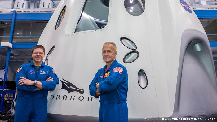Astronauts Bob Behnken and Doug Hurley stand next to the Crew Dragon spacecraft