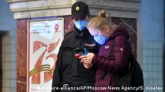 Женщина-полицейский проверяет пропуск у прохожей