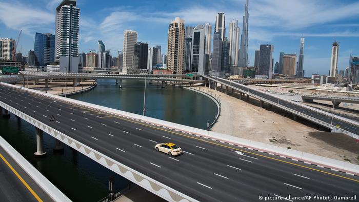 A lone taxi cab drives over a typically gridlocked highway with the Burj Khalifa, the world's tallest building, in the skyline behind it in Dubai.
