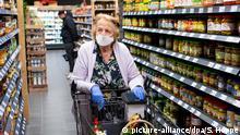 01.04.2020, Bayern, Neubiberg: Eine Frau trägt bei ihrem Einkauf in einem Supermarkt einen Mundschutz. Foto: Sven Hoppe/dpa | Verwendung weltweit