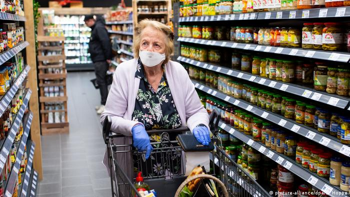 A gloved woman pushing a trolley down a supermarket aisle while wearing a coronavirus protection face mask during the global COVID-19 pandemic