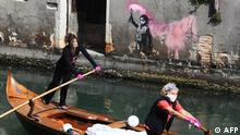 Two women members of Row Venice , a non-profit organization dedicated to preserving the traditional Venetian rowing style, rows on a gondolini boat, past a Banksy artwork as they deliver food to families who do not have the opportunity to go to buy food, on April 18, 2020 in the Venice's canal. - Parts of Europe moved cautiously to reopen their streets and economies on April 16, 2020, but the coronavirus pandemic (COVID-19) was far from beaten and the World Health Organization warned the continent was still in the eye of the storm. (Photo by ANDREA PATTARO / AFP) / RESTRICTED TO EDITORIAL USE - MANDATORY MENTION OF THE ARTIST UPON PUBLICATION - TO ILLUSTRATE THE EVENT AS SPECIFIED IN THE CAPTION