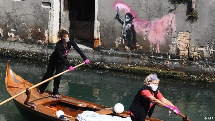 Dos mujeres de la organización sin fines de lucro Row Venice, dedicada a preservar el estilo tradicional de remo veneciano, recorren los canales de Venecia en un bote gondolini para entregar comida a familias que no tienen la oportunidad de salir a comprarla. En el fondo se aprecia una obra del mundialmente afamado artista callejero británico Banksy.