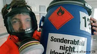 Im Labor der Sonderabfall-Sammelstelle auf der Deponie Schwerborn hält ein Mitarbeiter in Schutzkleidung ein Fass mit nicht bekannten Sonderabfällen (Foto: dpa)
