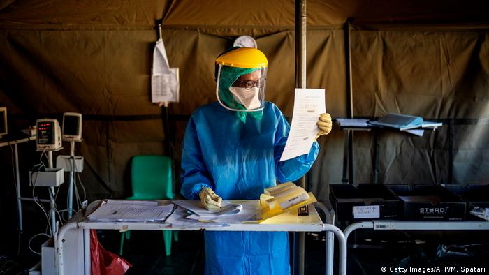 A woman wearing a protective suit sits at a table