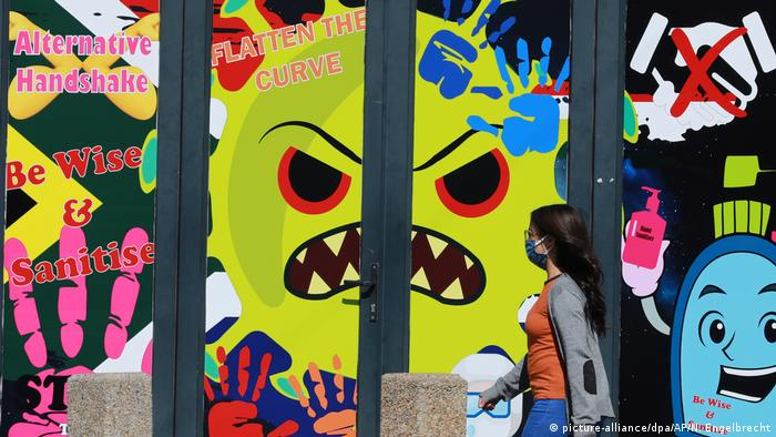 A woman with a face mask walks by graffiti showing the coronavirus in Cape Town