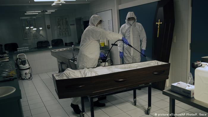 Workers, wearing a full protective equipment, disinfect the casket of someone who has died of coronavirus at the Fontaine funeral home during a partial lockdown to prevent the spread of coronavirus in Charleroi, Belgium,