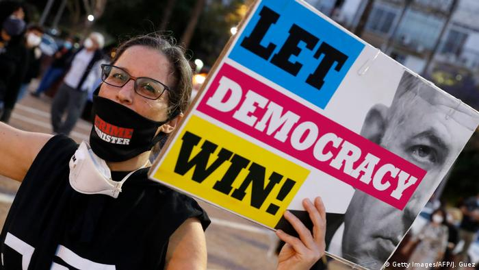 A protester in Tel Aviv holds a sign that reads let democracy win (Getty Images/AFP/J. Guez)