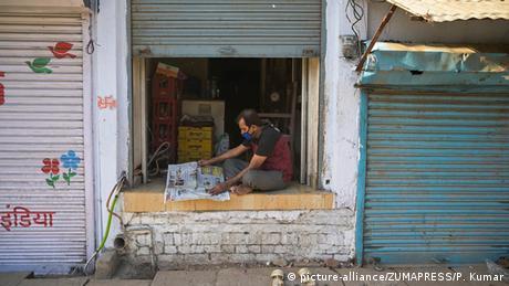 A shopkeeper reads the newspaper at his shop during lockdown in wake of Coronavirus pandemic in Prayagraj, Uttar Pradesh, India