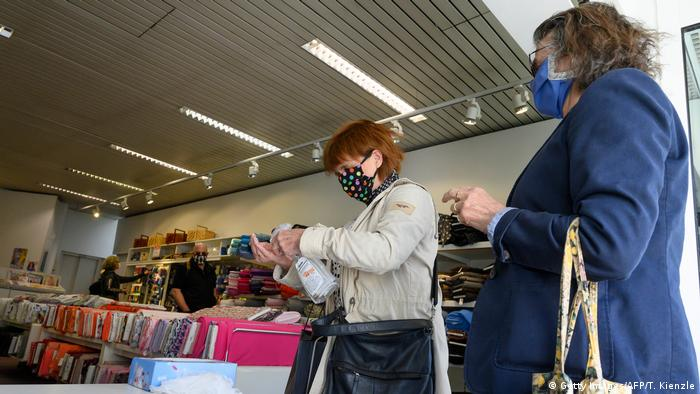 Woman wearing face masks disinfect their hands as they enter a fabrics store in Ludwigsburg, southern Germany, on April 20, 2020, amid the novel coronavirus COVID-19 pandemic. - Parts of Europe hit hard by the deadly coronavirus pandemic took tentative steps towards resuming normal lives on Monday, April 20, 2020, with Germany allowing some shops to reopen. (Photo by THOMAS KIENZLE / AFP)