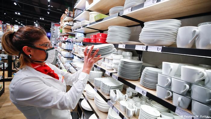 Seorang pegawai toko perabotan rumah tangga di Pulheim, NRW, menggunakan masker saat merapikan rak toko.
