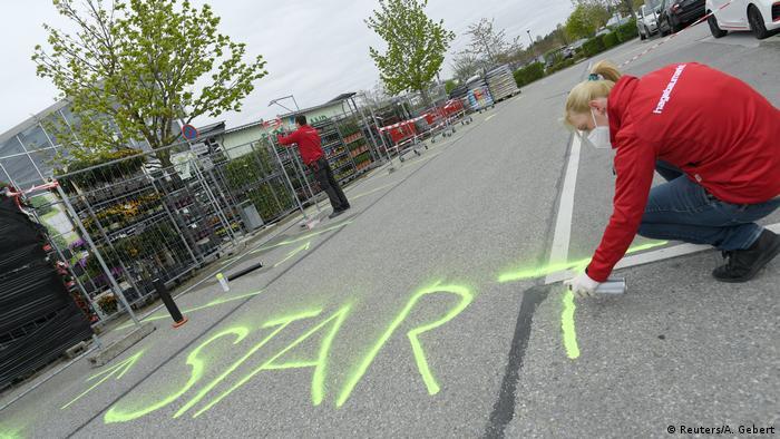 Karyawan toko di Jerman melukis jalan dengan tulisan Start sebagai titik awal antrian. Toko-toko kembali buka dan tetap mengingatkan pembeli akan pembatasan sosial.
