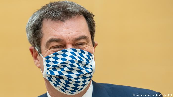 Markus Söder sporting a face mask with Bavarian flag pattern