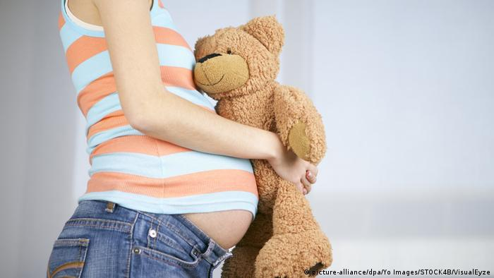 O gravidă foarte tânără cu un ursuleț de pluș