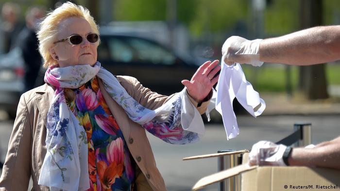 Una señora recibe mascarillas reutilizables.