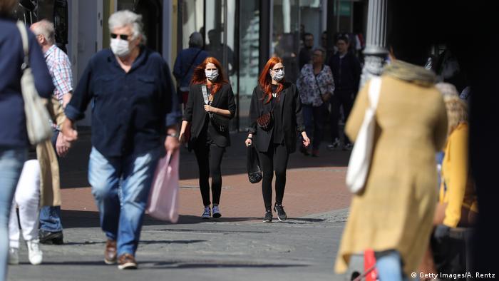 Para pembeli berjalan di kawasan kota Bonn, NRW, setelah Jerman mengizinkan toko dengan luas di bawah 800 meter persegi dibuka kembali.