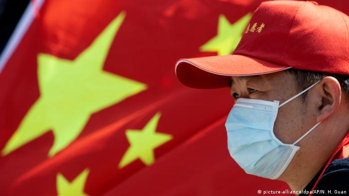 A Chinese person with a facemask and the Chinese flag in the background