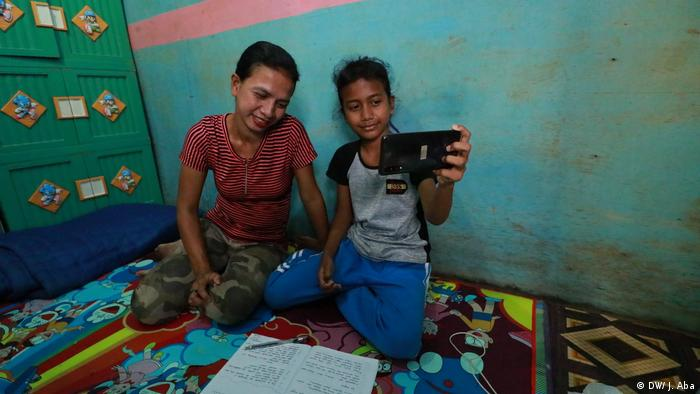 Dewi Yulianti (left) and Esa Dwinov (right) look at a cellphone in their home