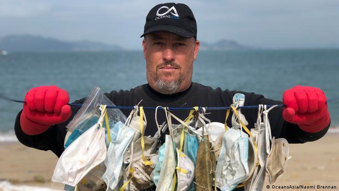 Gary Stokes, del grupo conservacionista OceansAsia sosteniendo mascarillas quirúrgicas encontradas en las islas Soko.