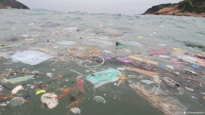 A surgical mask floats in the sea among dense plastic pollution