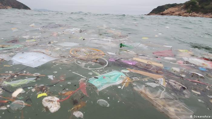 Una mascarilla quirúrgica flotando en el mar entre la densa contaminación plástica.