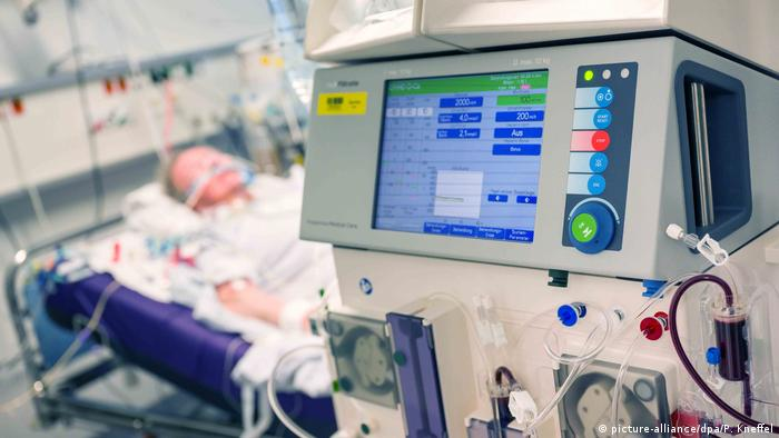A patient lies in an intensive care bed in a hospital in Munich