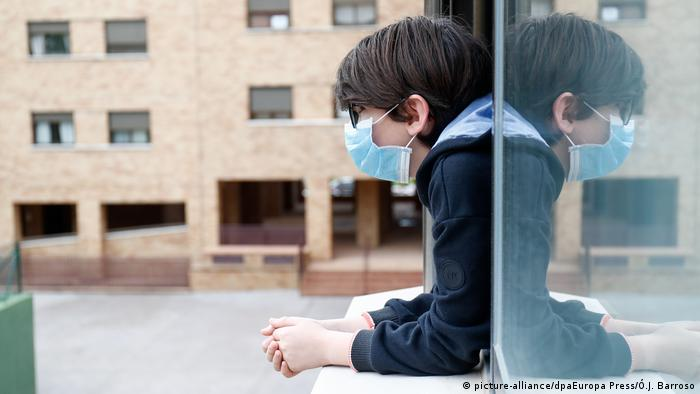 Coronavirus in Spain: a young child with a face mask stares out the window.