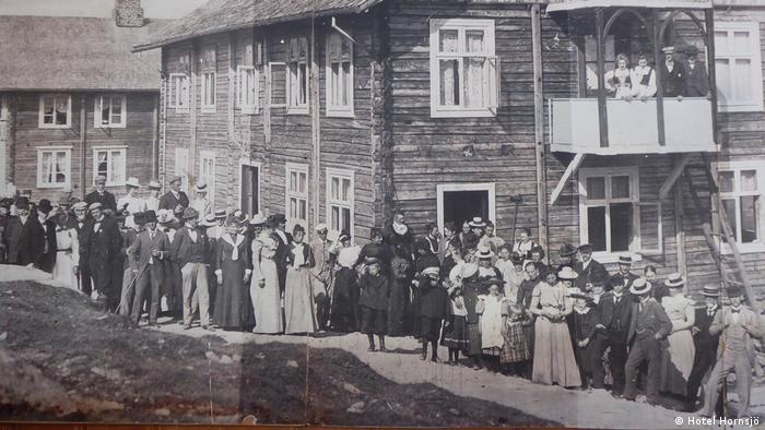 Auf dem Schwarzweißfoto steht eine lange Schlange von festlich gekleideten Frauen und Männern vor einem großen Holzhaus. Zwei Frauen und zwei Männer stehen auf einem Balkon im ersten Stockwerk. Im Hintergrund steht noch ein zweigeschossiges Holzhaus. Nach Angaben des Hotels Hornsjö handelt es sich um eine Festgesellschaft im Jahr 1903.