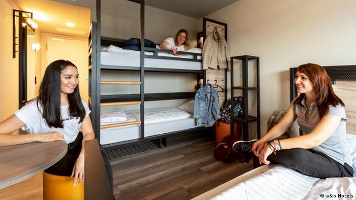 Drei junge Frauen teilen sich ein Mehrbett-Zimmer im a&o Hostel Wolfgangs in Salzburg. Links im Hintergrund befindet sich der Ausgang. Die Decken- und Wandlampen zu einem kleinen Vorraum des Zimmers sind eingeschaltet. Links gibt es einen Spiegel und eine Wandgarderobe, rechts Fächer für Kleidung und Gepäck. Links im Vordergrund sitzt eine der Drei mit langen dunkelbraunen Haaren auf einem ocker farbenen Hocker und lehnt den rechten Unterarm auf einen runden Bartisch. Sie schaut auf die Frau, die ebenfalls lächelt und mit einem angewinkelten Bein auf einem Bett sitzt.Die Brünette trägt mehrere dünne Armbänder an der linken Hand. Im Hintergrund liegt auf dem oberen des Etagenbettes eine weiter junge Frau, die sich mit der rechten Hand am Schutzgitter hält und dabei lächelt. An Bügeln an einer Holzwand hängen ein dünner Anorak und eine Jeansjacke. Davor steht ein runder Hocker und ein Regal mit der Etagen. Alle drei Frauen tragen kurzärmelige T-Shirts und dunkle Hosen.
