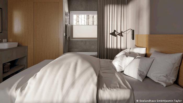 Blick in ein Schlafzimmer der Ferienanlage Seedorf bei Neuendorf im Bundesland Brandenburg bei Berlin. Die Sonne scheint und wirft Schatten auf die rechte Bildhälfte. Rechts ein weißes Waschbecken, darunter eine Holzkonsole. Links im Hintergrund eine Kabine aus hellerem Holz mit einer Tür, der Zugang zur Toilette. Hinter einem Vorhang: links an der Wand hängt ein Heizstrahler, daran ein Handtuch, darunter eine Badewanne. Aus dem oberen Rand des Fensters, der nicht mit der Jalousie verschlossen ist, hat man den Blick auf Baumstämme im Wald der Anlage. Im Vordergrund ist ein Doppelbett mit fünf Kissen und Decken. Das Kopfteil besteht aus hellem Holz. An der Wand hängt eine ausziehbare Lampe. Die Farben des Interieurs sind in Naturtönen gehalten.