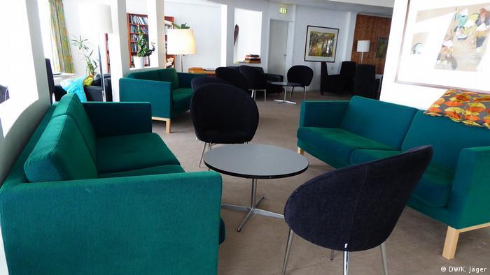 Drei Sofas mit grün-türkis leuchtendem Stoff, mehrere schwarze Designer-Sessel, runde Tische, Stehlampen mit weißem Schirm, ein Wandbild am rechten Bildrand und an der Wand im Hintergrund steht ein braunes, gefülltes Bücherregal. Alles aus zweiter Hand/ Secondhand. Gespendet von Norwegens Luxushotels für das Hotel Hornsjö.